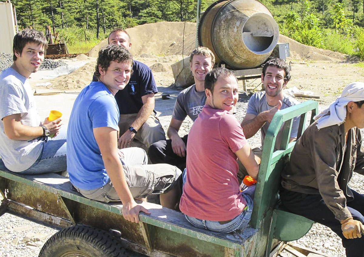 six volunteers riding tractor in north korea