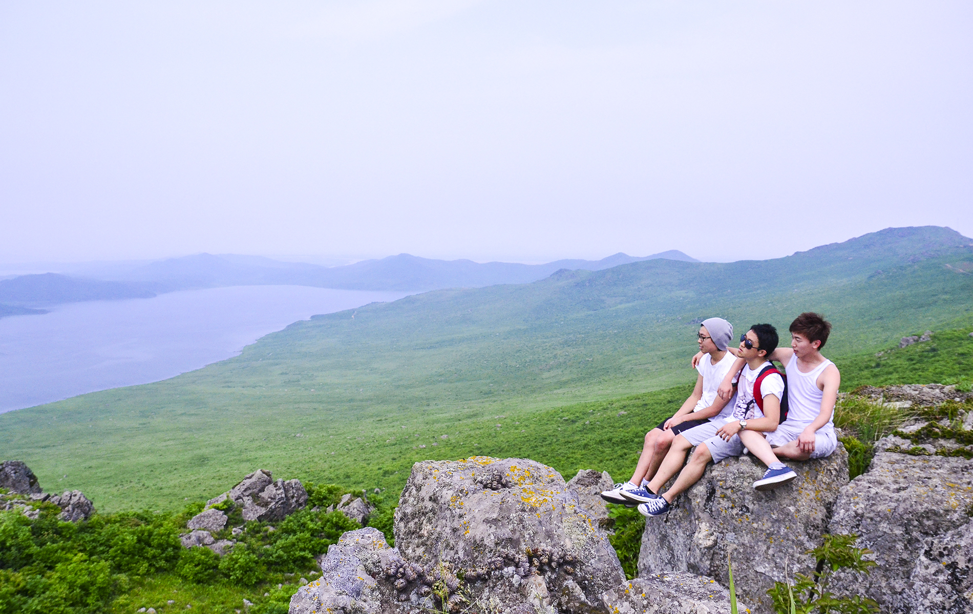 tourists sitting on large rock