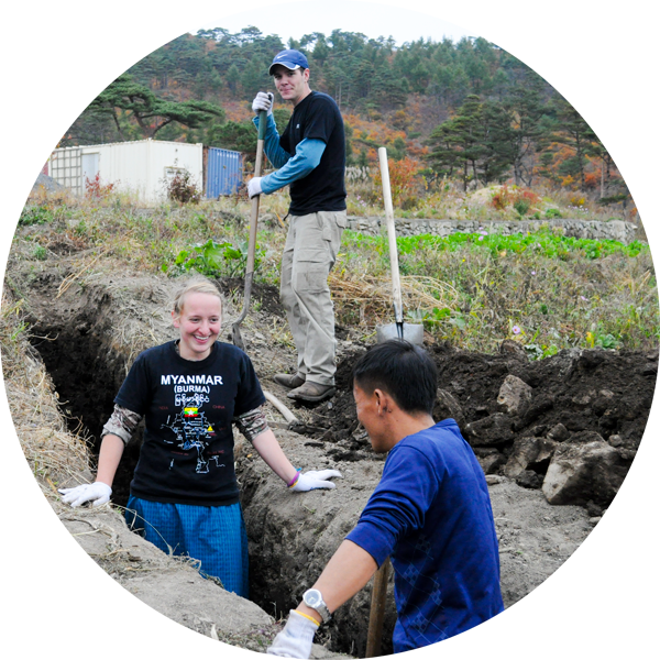 three people digging ditch